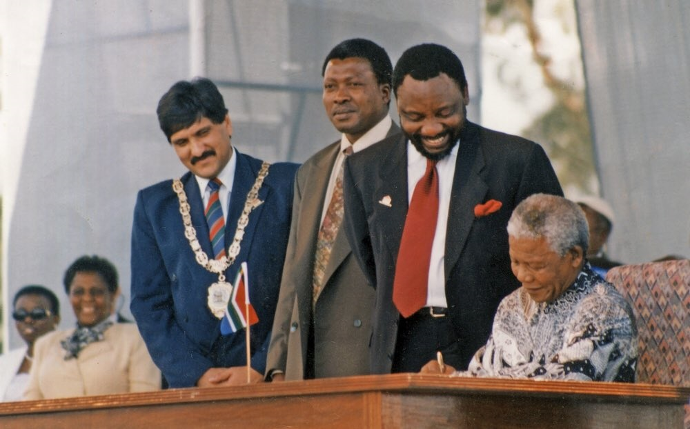 President Nelson Mandela signs the country's new constitution while ANC's chief negociator during the drafting process, Cyril Ramaphosa looks on, at Sharpeville stadium near Vereeniging on 10 December 1996.