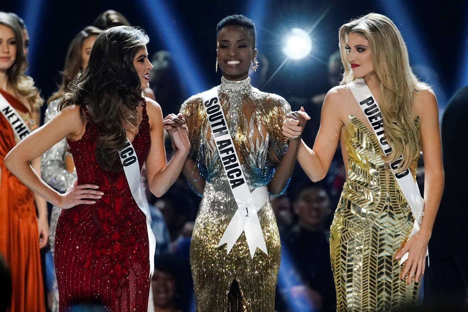 Madison Anderson, of Puerto Rico, Miss Universe 2019 Zozibini Tunzi and Sofia Aragon of Mexico hold hands in the Miss Universe pageant. Picture: Elijah Nouvelage/Reuters