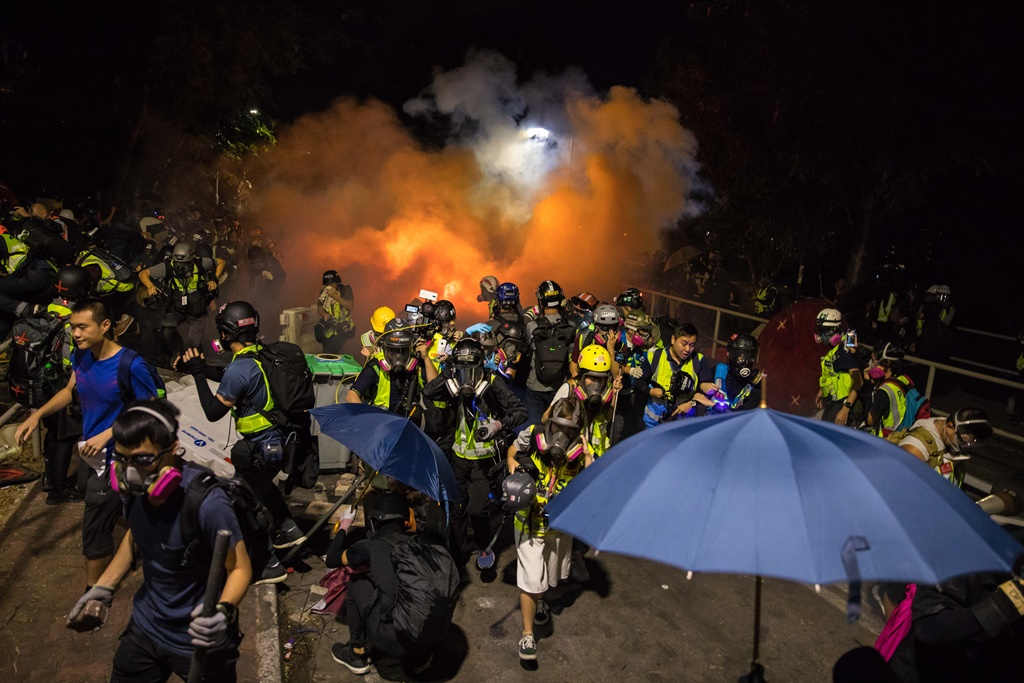 Protesters and journalists react after police fired tear gas at the Chinese University of Hong Kong (CUHK), in Hong Kong. (AFP)
