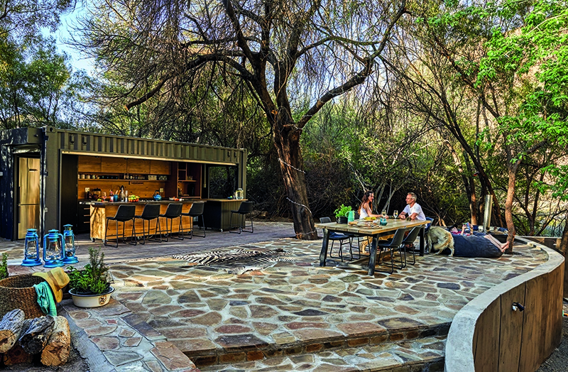 Caren and Dave are thrilled with their boma under the trees. They have always enjoyed camping next to the river on their farm, but now they can cook and socialise in comfort. Table from Holly Wood Furniture; dining chairs and bar stools from Cielo; kitchenware from Le Creuset, CulinaryKraft and Yuppiechef; fridges from Takealot; sinks and taps from The House Shop