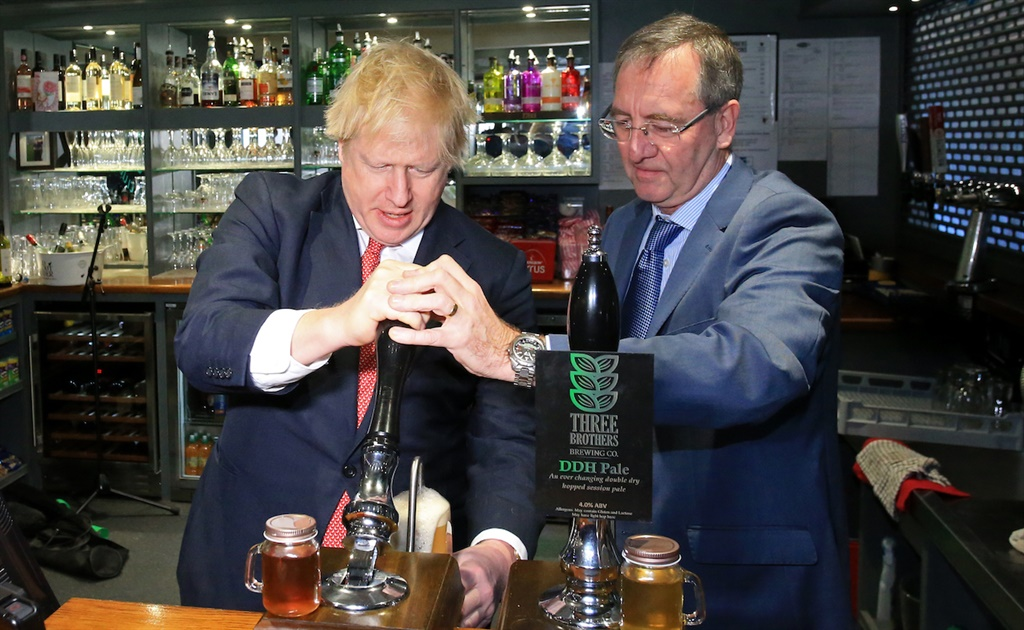 UK Prime Minister Boris Johnson (L) pulls a pint with newly elected Conservative party MP for Sedgefield, Paul Howell at Sedgefield Cricket Club in County Durham on December 14, 2019  (Photo by Lindsey Parnaby - WPA Pool/Getty Images)