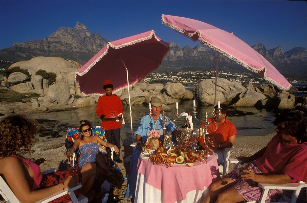 A black man serves drinks at a beach party on Clifton Beach, Cape Town, South Africa, circa 1990. (Photo by Romano Cagnoni/Getty Images)