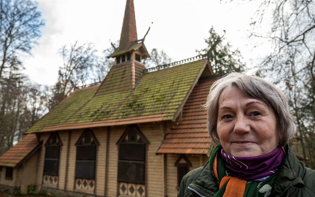 Regina Bierwisch poses next to the Stabkirche, in a wooded area outside the town of Stiege, Saxony-Anhalt, eastern Germany, on 19 November 2020.