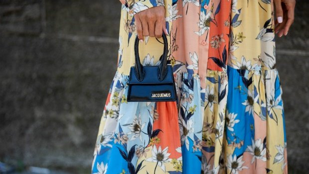 A guest is seen wearing dress with floral print, mini Jacquemus bag during Paris Fashion Week. Photo by Christian Vierig