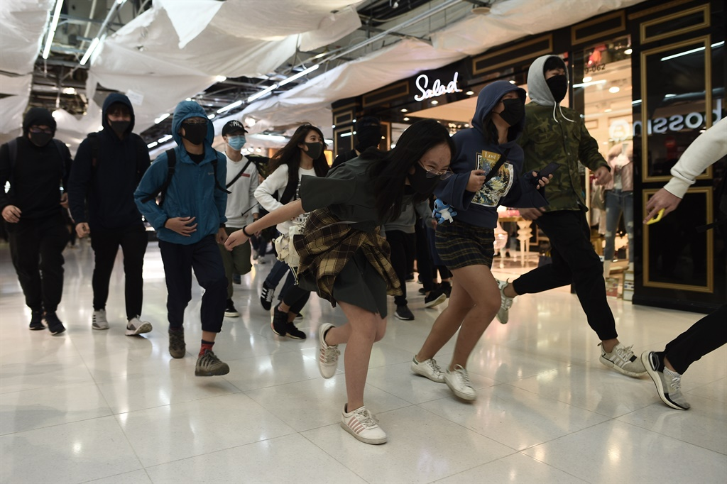 People practice running as they take part in a march through a shopping mall in the Tai Po district in Hong Kong on December 26, 2019. (Philip FONG / AFP)
