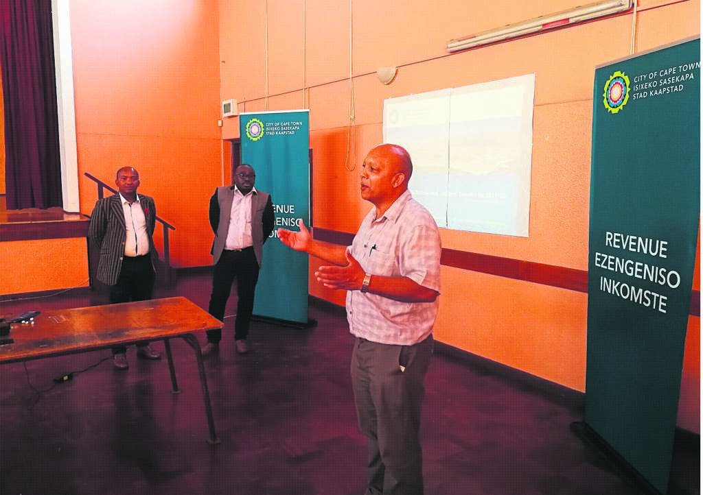 Three revenue officials from the City of Cape Town's Plumstead regional office attended the meeting. Addressing residents is Keith Adams while Luvo Mshumpela and Sonwabile Mazinyo listen in the background.