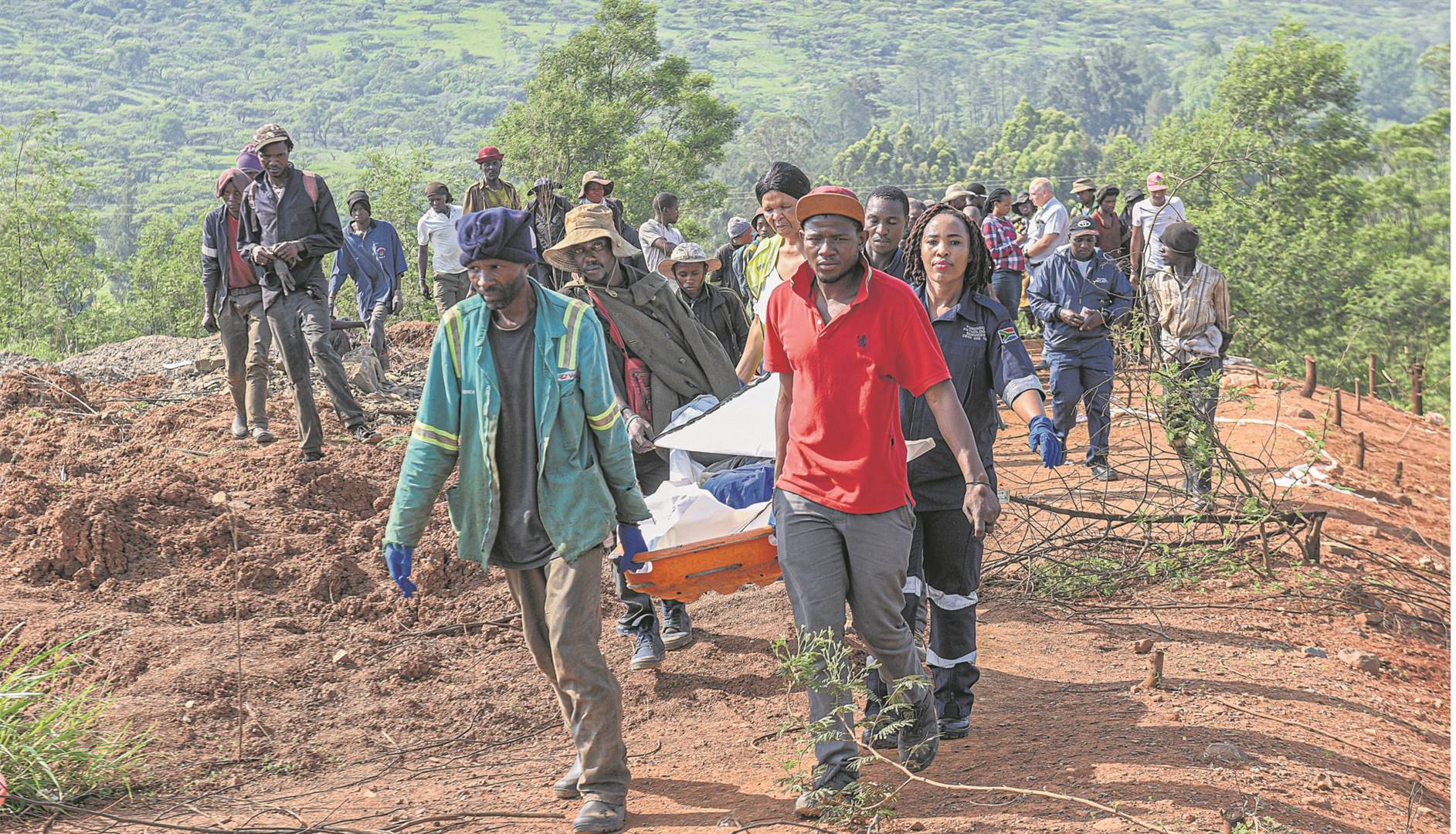 Aarone Limo (in the red shirt) and waste-pickers help the forensic pathology team carry the body of his cousin, Khabutiele Moahloli, from where he was found murdered at the New England Road landfill site on Tuesday morning.
