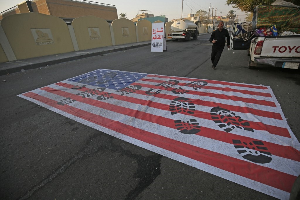 A mock US flag is laid on the ground for cars to drive on in the Iraqi capital Baghdad on January 3, 2020, following news of the killing of Iranian Revolutionary Guards top commander Qasem Soleimani in a US strike on his convoy at Baghdad international airport.