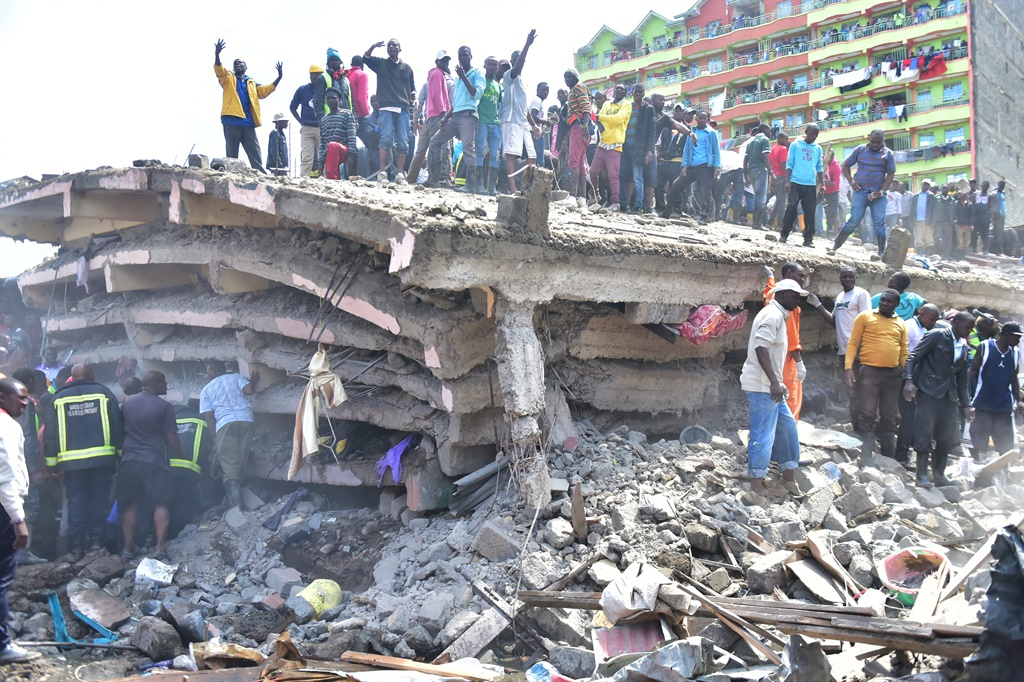 People stand on top of a collapsed six-storey building, as search and rescue continue in Nairobi, (AFP)