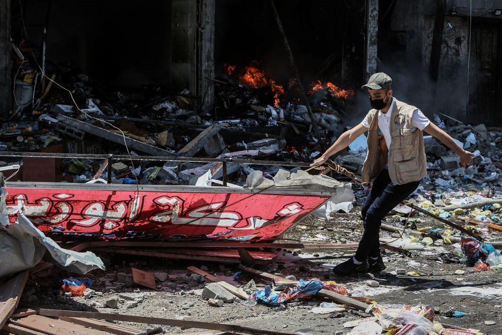 Amember of the Palestinian Civil Defense works at a site hit by an Israeli airstrike on Rafah, amid the escalating flare-up of Israeli-Palestinian violence. (Photo by Abed Rahim Khatib/picture alliance via Getty Images)