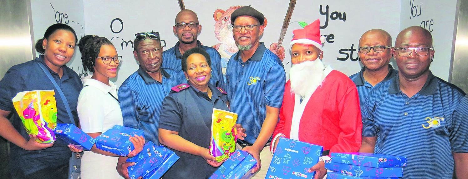 The Tough Guys Club, a 24-member social and investment club in Bloemfontein, brought a smile to the faces of children in the paediatric ward of the Pelonomi Hospital by donating Christmas gifts for those between the ages of seven and 14. From the left are Zama Shozi, Joy Tshabalala, Lebo Thinane, Daddy Maseola, Judy Seboko, Lerato Sethibe, Amos Mkam (Santa Claus), Page Phajane and Teboho Manaka. The gifts, purchased with proceeds generated by the club, were handed over to the nursing staff, who were equally delighted with the generous gesture, on Saturday (07/12).  Photo: Teboho Setena