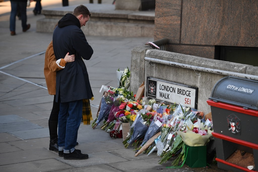 A couple place a bouquet of flowers on London Bridge in memory of the victims of the knife attack at the end of November. (Daniel Leal-Olivas/AFP).