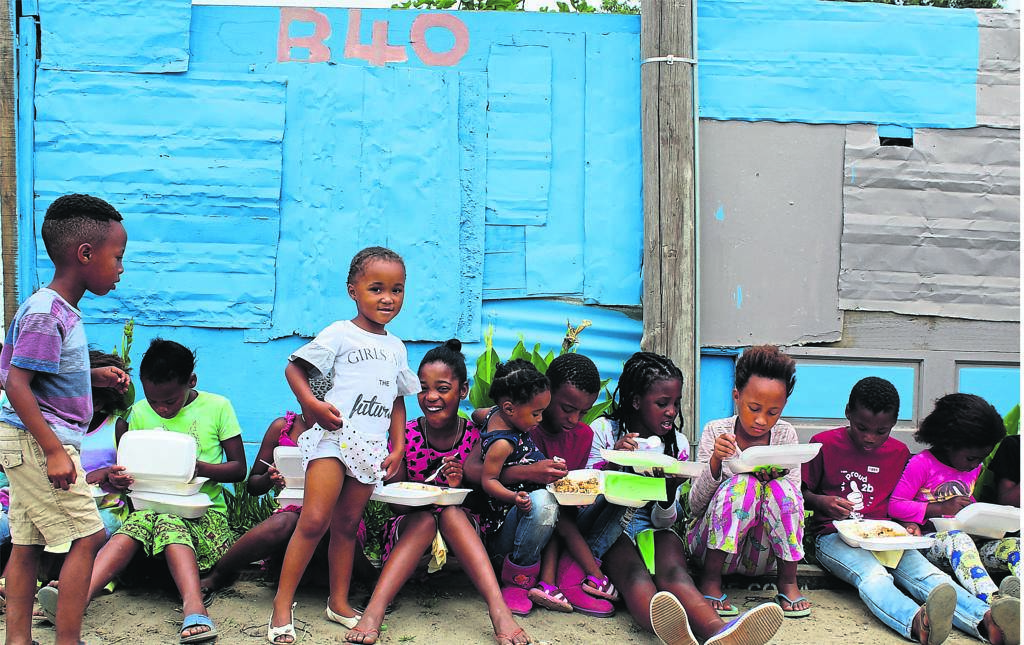 Kids from Bonnytoun tuck into the chicken stew and rice donated by Wynberg police officers.PHOTO: Nettalie Viljoen