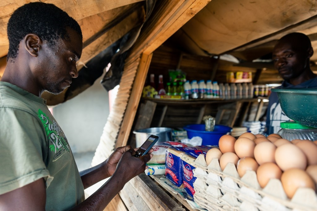 Aaron Munyoro, who is unemployed and lives with his elderly mother, makes a payment from his mobile phone for basic food items including bread at a local tuck shop in Epworth, on the outskirts of Harare, on December 10, 2019.