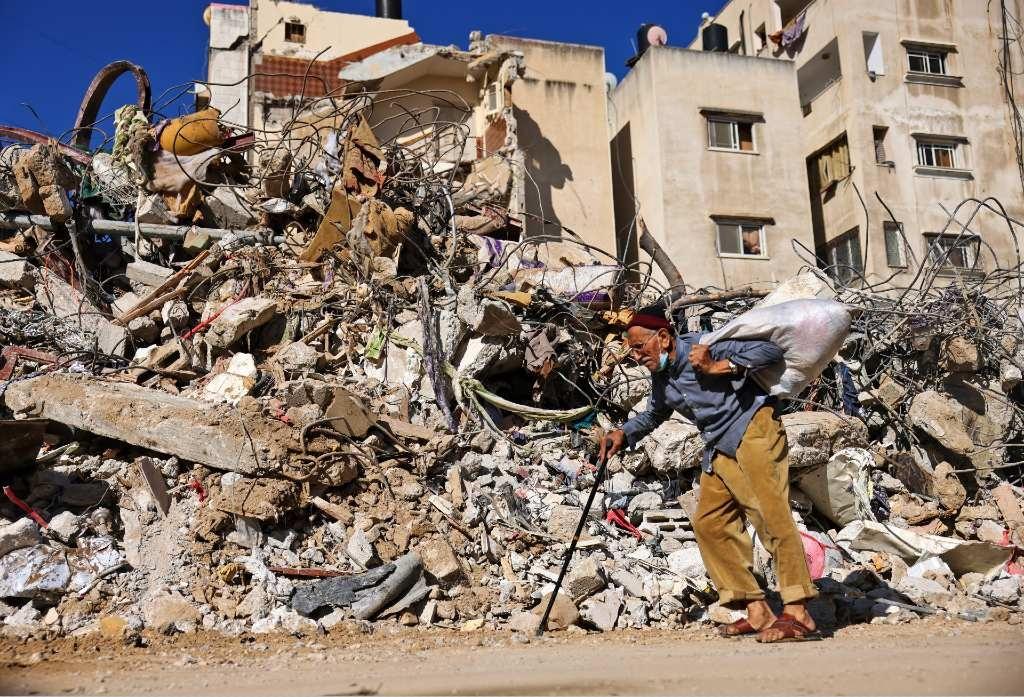 A Palestinian elderly man walks past a destroyed b
