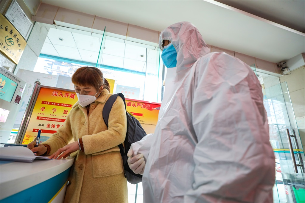 A suspected coronavirus patient fills out a form at a community health station before being transferred to a hospital in Wuhan.
