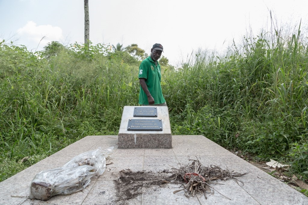 Louis Marie Mang, a UPC (The Union of the Peoples of Cameroon) activist, stands next to the tomb of Ruben Um Nyobé, in Eseka, on December 11, 2019.