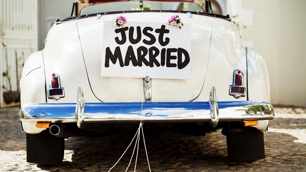 """""""Just Married"""" sign and cans attached to convertible car's trunk. Horizontal shot."""