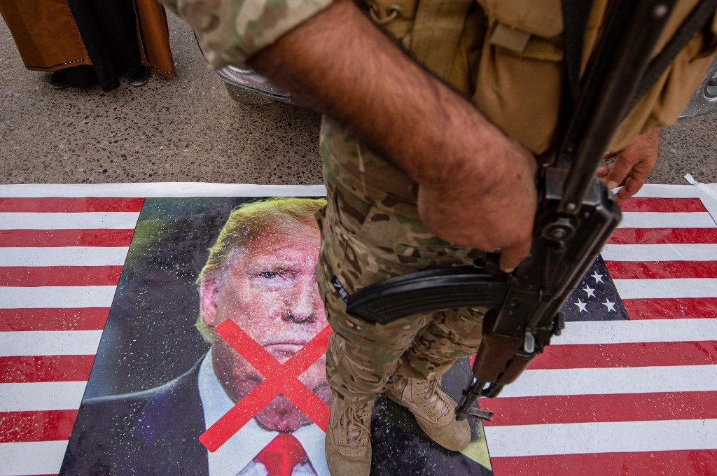 A member of Iraq's Hashed al-Shaabi paramilitary network stands on a US flag during a symbolic funeral procession for the network's deputy Abu Mahdi al-Muhandis in the southern city of Basra, on January 4, 2020.