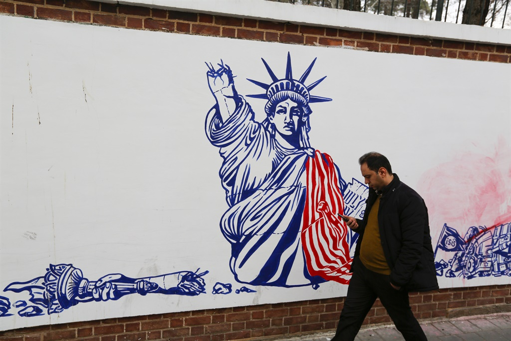 An Iranian man walks past a mural painted on the walls of the former US embassy in the capital Tehran. (Atta Kenare, AFP)
