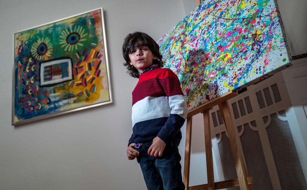 "7-year-old German artist Mikail Akar poses in front of a print edition of his ""Champi"" painting (R) and his painting ""Sonnenblume Mensch"" (Sunflower Man) (L) prior to the opening of his ""Manus 11"" exhibition in Berlin. (John MacDougall, AFP)"