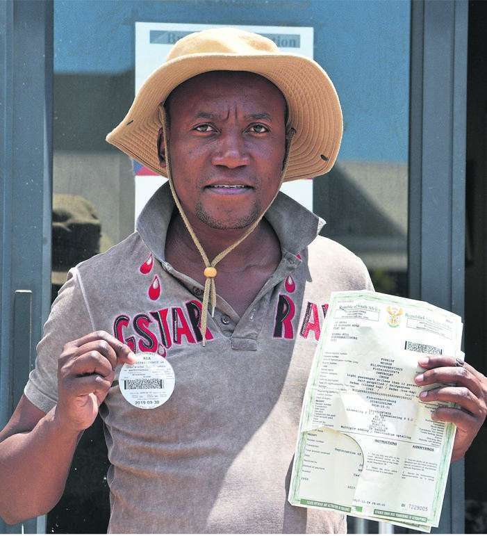 Themba Nkuna holds up his old licence disc just before he joined the long queue at the Scottsville Post Office to renew it.