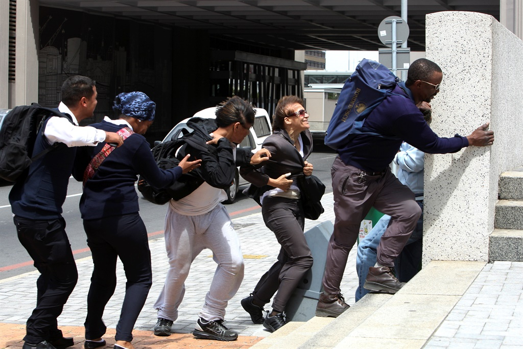 People struggle to keep balance during strong winds in the Cape Town CBD. (Photo by Gallo Images / The Times / Esa Alexander)