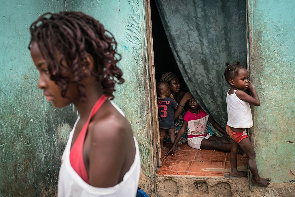 A mother braids her daughters hair in a poor neighbourhood overlooking Cabinda, Angola. (Nichole Sobecki for The Washington Post via Getty Images)