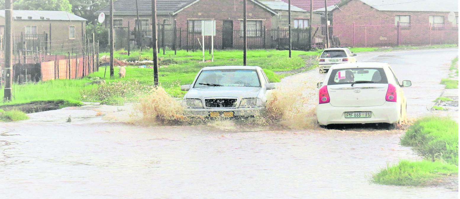 Motorists driving along a flooded road in Turflaagte, Bloemfontein. The road was flooded after a cloudburst that caused havoc in adjacent residential areas on Saturday (25/01). While some motorists navigated their way through the water, others sped through, ignoring potential danger. Photo: Teboho Setena