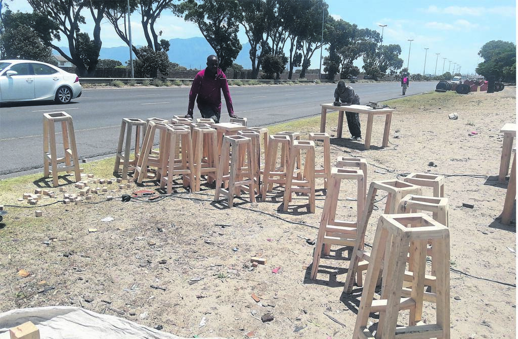 Philip Mamvura showing off some barstools he is making. Cuthbert Tambo leans on the table behind. PHOTO: UNATHI OBOSE