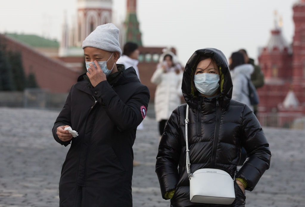 Tourists wear protective face masks as they walk i