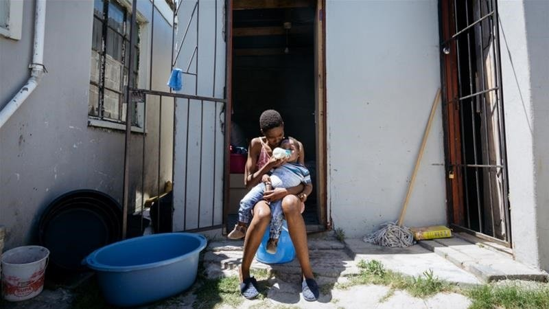 Luthando sits with her one-year-old son Bandile in their one-room home in Phillipi, Cape Town. (Yeshiel Panchia, Al Jazeera)