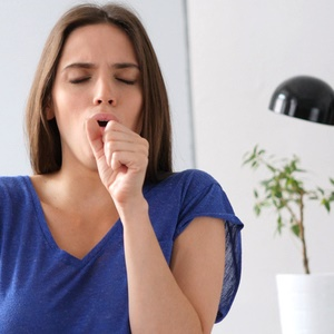 Woman coughing at work
