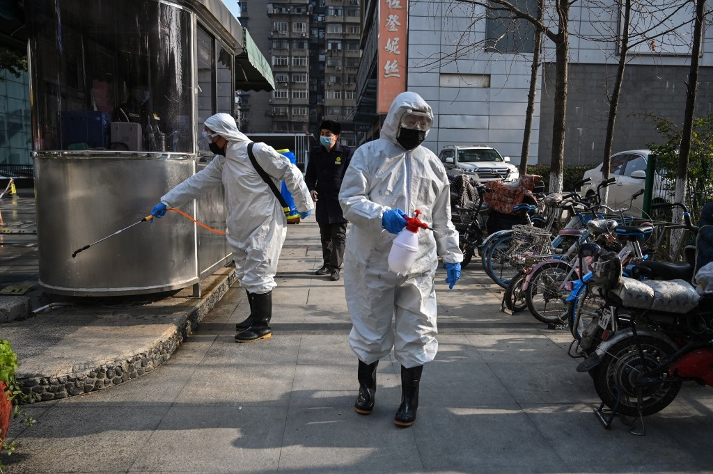 People dressed in protective clothes disinfect an area in Wuhan, in Hubei province. (Hector Retman/AFP).