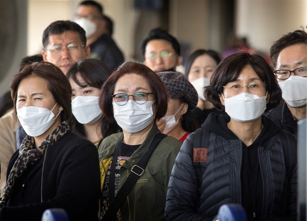 Passengers on a flight from Asia wear face masks to protect against the spread of the Coronavirus. (Mark Ralston/AFP)