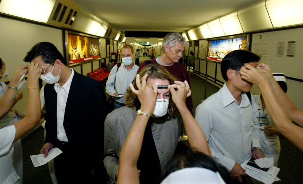Thai nurses and doctors check temperatures of travelers coming from Hong Kong at the Bangkok International Airport. ( Paula Bronstein/Getty Images)