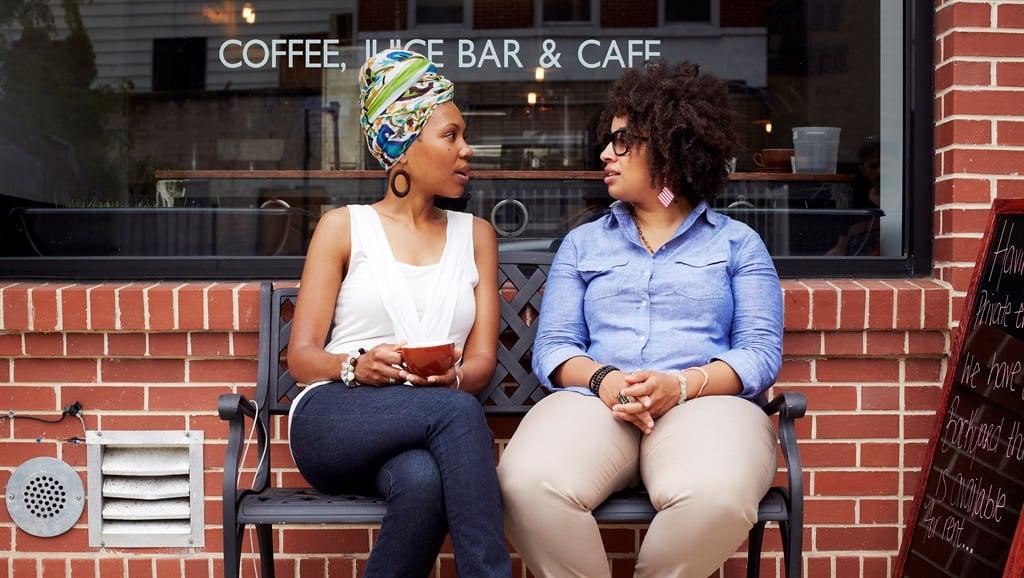 Women talking outside coffee shop on city street