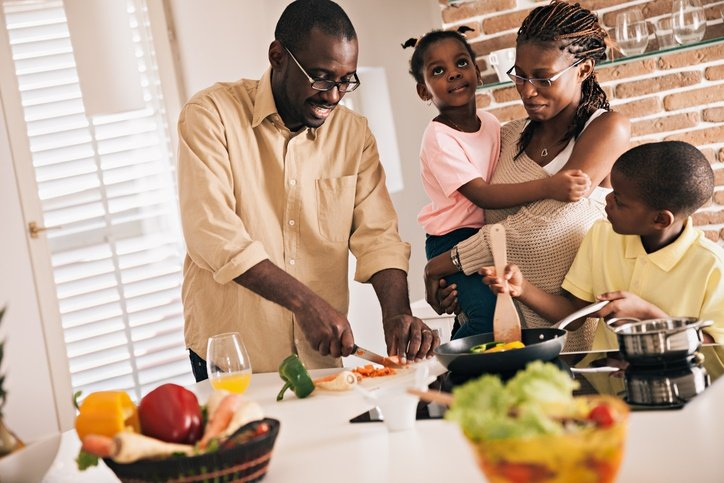 Close up of a happy family preparing food in kitch