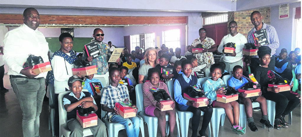 Some of the learners with their new school shoes and stationery during the event while teachers and donors are looking on. PHOTO: UNATHI OBOSE