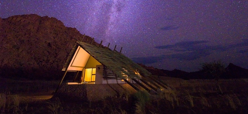 Milky way over a small chalet of a desert lodge ne