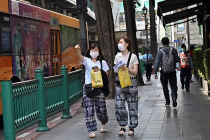Tourists wear protective facemasks while walking a