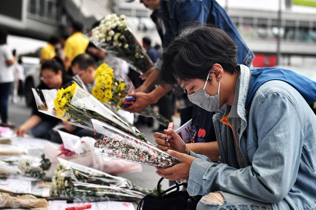 Mourners lay flowers at the Terminal 21 shopping mall, where a mass shooting took place.