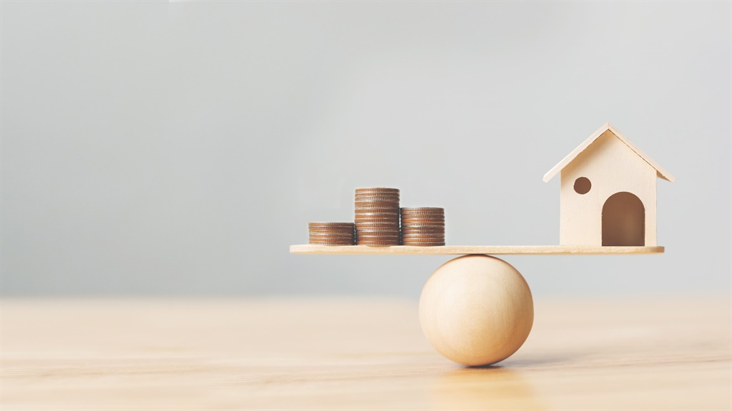 Wooden home and money coins stack on wood scale. P