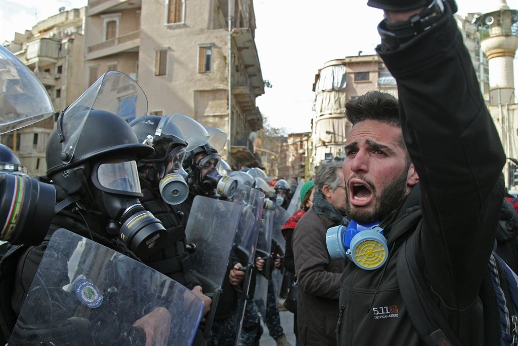 Lebanese Protesters chant slogans during clashes with the security forces, as they gather on in the heart of Beirut to stop a confidence vote for a new government, which they say fails to address their demands and cannot rescue the ailing country. (AFP)