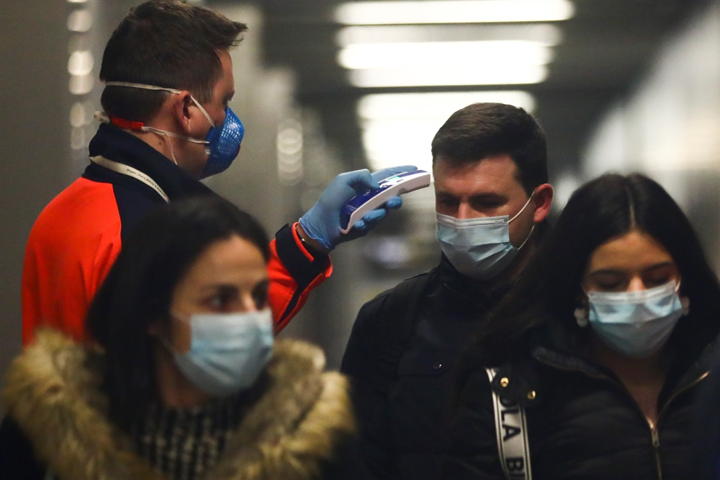 Health personnel monitors the body temperature of passengers who arrived in a flight from Milano, Italy to Krakow Airport in Balice, Poland in February 2020. (Photo by Beata Zawrzel/NurPhoto via Getty Images)