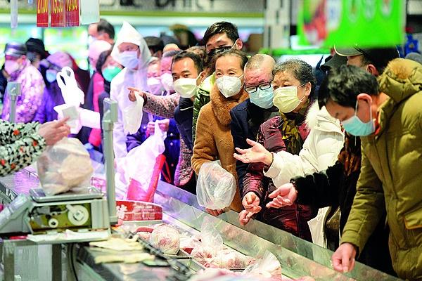 Inwoners met gesigmaskers staan in lang toue om be