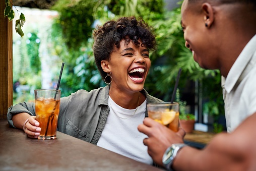 Shot of a happy young couple having drinks and rel