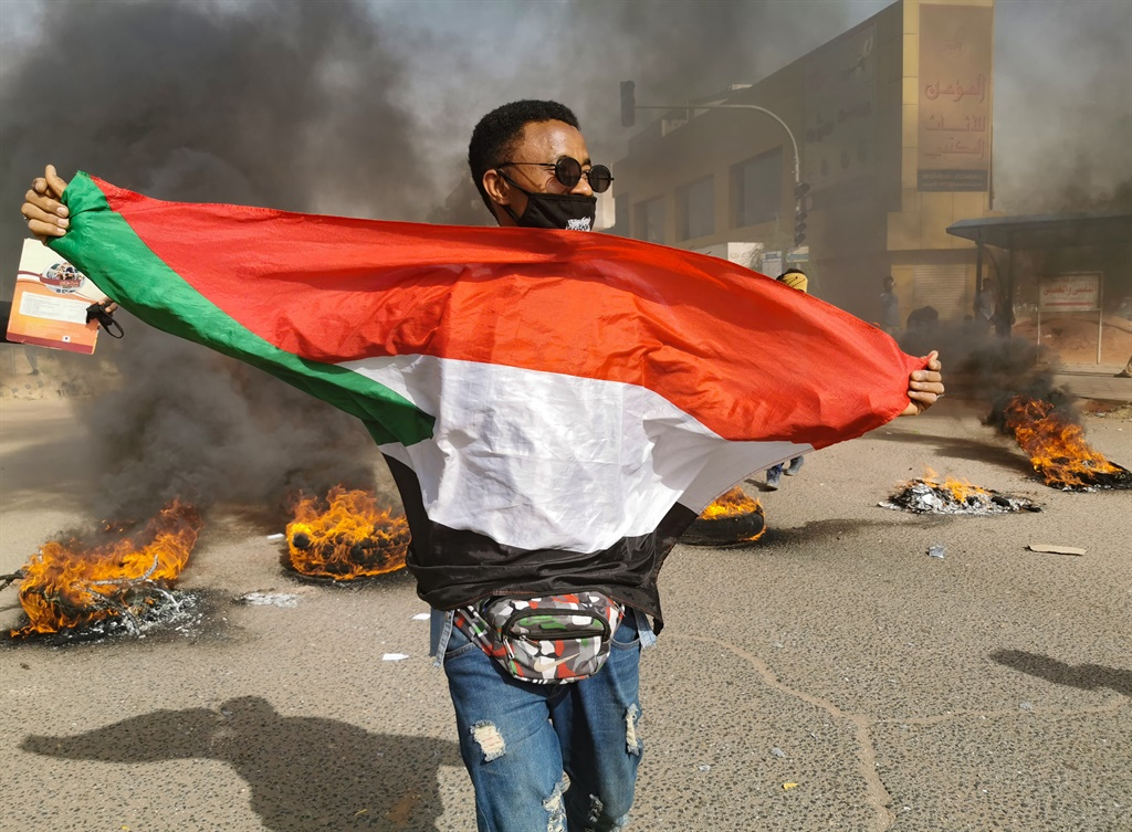 A Sudanese protester carries a national flag as others burn tyres in the centre of the capital Khartoum during a demonstration calling for the reinstatement of soldiers who were forced into retirement after they voiced support for last year's revolution. (AFP)
