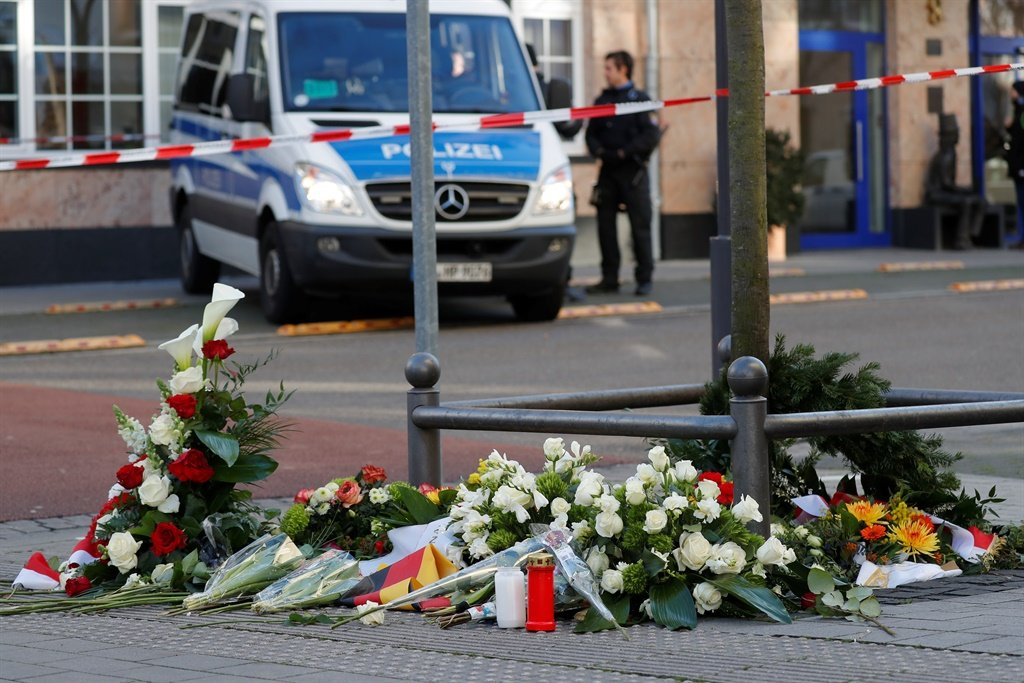 A police car is seen behind flowers placed at a makeshift memorial for the victims of the Hanau shooting in front of a shisha bar in Hanau near Frankfurt am Main, western Germany. (AFP)