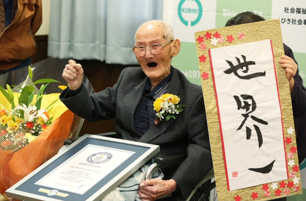 112-year-old Japanese man Chitetsu Watanabe poses next to calligraphy reading in Japanese 'World Number One' after he was awarded as the world's oldest living male